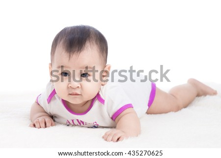 happy laughing child lies on stomach, 6 months old asian baby girl - stock photo