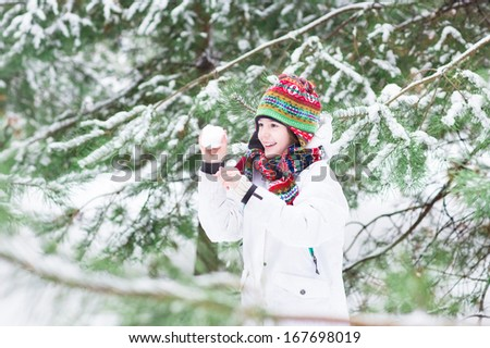 Happy laughing child playing snow ball fight in a snowy winter forest - stock photo