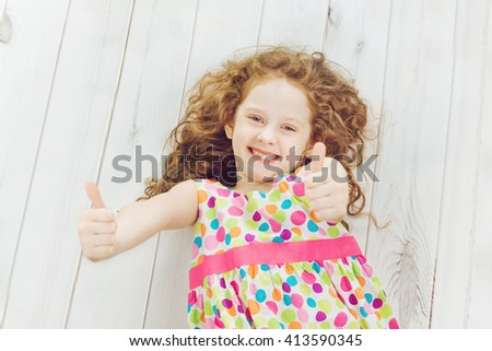 Happy laughing child with showing thumbs up. Happy childhood, travel, vacation, healthy lifestyle concept. High top view. - stock photo
