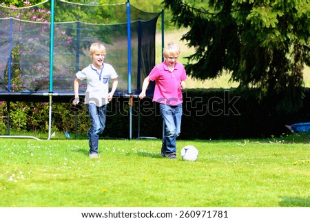 Happy laughing children, twin teenage boys, playing soccer in the garden at the backyard of the house on sunny summer vacation day - stock photo