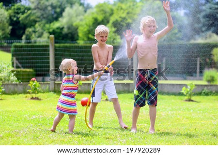 Happy laughing children, two young school boys and adorable toddler girl, enjoying hot sunny summer vacation day playing outdoors in garden at the backyard of the house spraying water from the hose