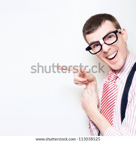 Happy Laughing Computer Geek Wearing Stereotype Glasses, Striped Tie And Pointing To Blank Wall Advertising Copyspace