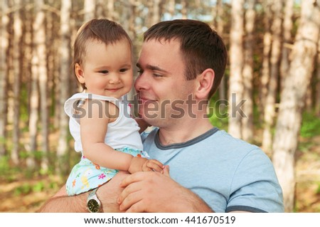 happy laughing family, daughter hugging father in nature. Father playing with his daughter on the meadow in summer day. Happy family resting - stock photo