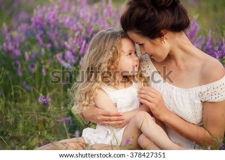 happy laughing family, daughter hugging mother in nature. Happy family resting on the poppy field. Mother playing with her toddler child. Happy joyful woman having fun with her baby girl in a field - stock photo