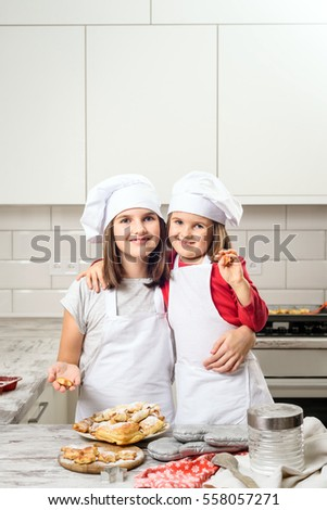 Happy laughing family preparation holiday food. Sisters making dough in white kitchen. Happy family in making cookies at home. Happy kids cooking healthy meal in the white kitchen.