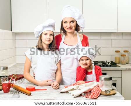 Happy laughing family preparation holiday food. Young beautiful mother and her cute daughter cooking Christmas cookies.