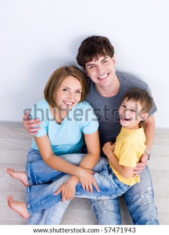Happy laughing family with young boy sitting on the floor in casuals - high-angle - stock photo