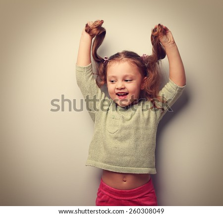 Happy laughing fashion kid girl playing with hair. Vintage portrait - stock photo