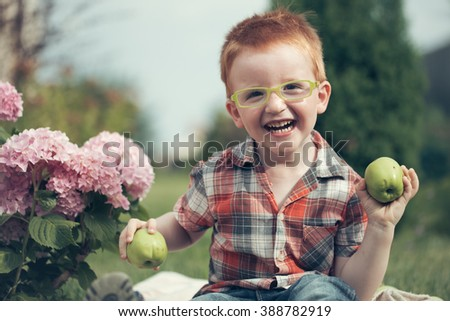 Happy laughing funny little red haired boy in stylish checkered shirt jeans and yellow glasses sitting outdoor on picnic with green apples near pink flowers on natural backdrop, horizontal picture - stock photo