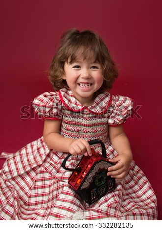 Happy, laughing girl, child in a Christmas dress, with christmas trees and ornaments on red background. X-mas happiness concept. - stock photo