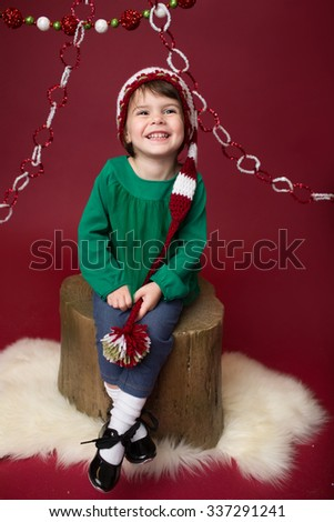 Happy, Laughing girl, Christmas in Santa Elf hat or winter holiday themed setup on red background, copyspace - stock photo