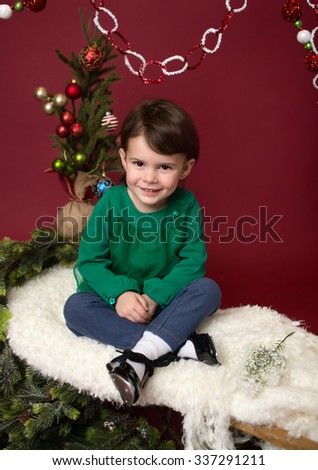 Happy, Laughing girl, Christmas or winter holiday themed setup on red background and sled, against christmas tree with ornaments, pine branches - stock photo