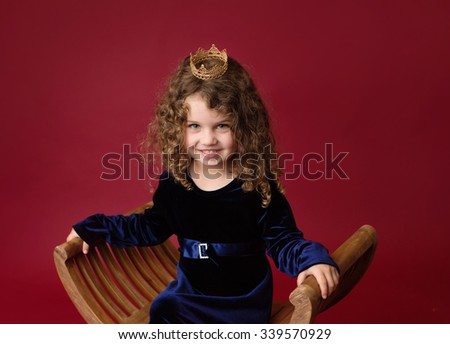 Happy, Laughing girl playing pretend as a princess, wearing a crown, red background - stock photo