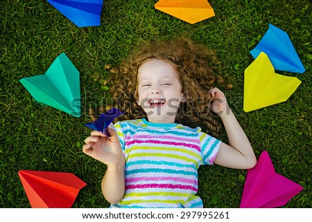 Happy laughing girl throwing paper airplane in green grass at summer park. Happy childhood, travel, vacation concept. Top view. - stock photo