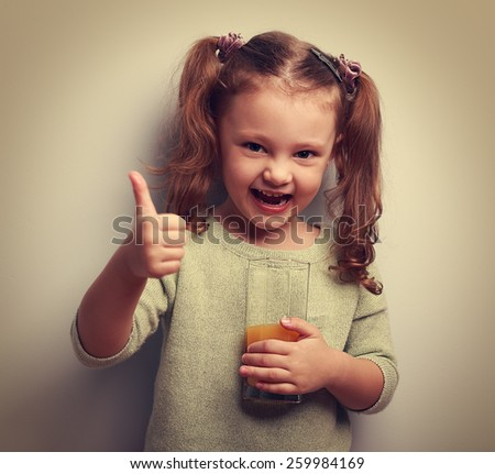 Happy laughing kid girl drinking juice and showing good sign. Vintage closeup portrait - stock photo