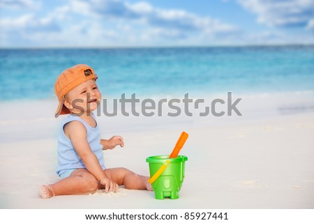 Happy laughing kid playing with scoop sitting near the ocean - stock photo