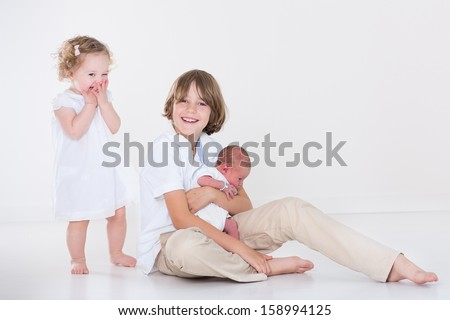 Happy laughing kids, a teen age boy and his adorable curly toddler sister playing with their new born baby brother in a white room with white clothes - stock photo