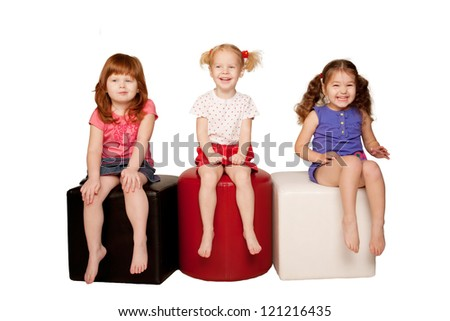 Happy laughing kids. Three beautiful girls sitting, looking at something and laughing. Isolated on white background - stock photo