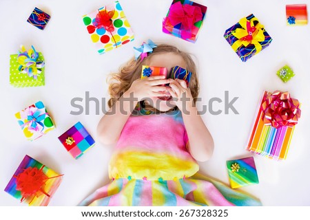 Happy laughing little girl, adorable toddler in a colorful party dress, holding many birthday presents, opening boxes decorated with ribbon and bow, excited to celebrate a family holiday - stock photo