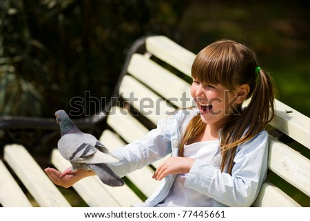 Happy laughing little girl feeding Pigeon sitting on hand - stock photo