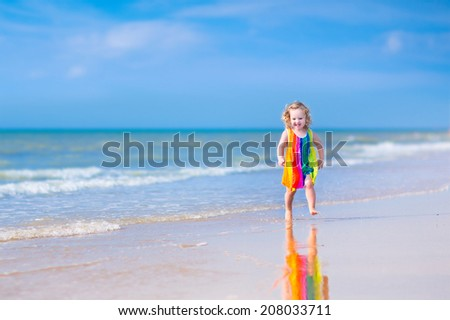 Happy laughing little girl in colorful rainbow bathing suit running and playing on ocean coast in water splashes on beautiful tropical island beach with turquoise clear water having fun on vacation - stock photo