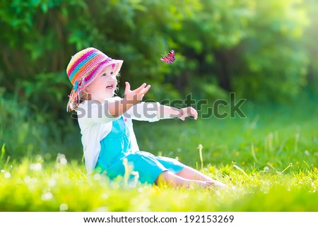 Happy laughing little girl wearing a blue dress and colorful straw hat playing with a flying butterfly having fun in the garden on a sunny summer day - stock photo