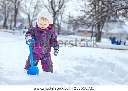 Happy laughing little girl wearing a purple down jacket and white knitted hat playing and running in a beautiful snowy winter park on Christmas day - stock photo