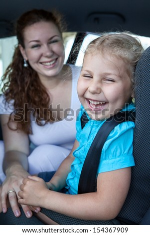 Happy laughing mother with small daughter in car safety seat - stock photo