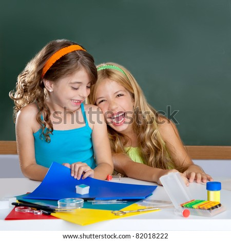 happy laughing student girls group at school classroom desk - stock photo