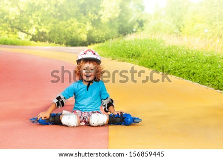 Happy laughing thee years old boy with rollerblades resting sitting on the road in the park on sunny summer day - stock photo