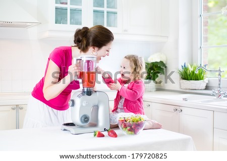 Happy laughing toddler girl and her beautiful young mother making fresh strawberry and other fruit juice for breakfast together in a sunny white kitchen with a window - stock photo