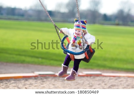 Happy laughing toddler girl swinging on a playground on a sunny spring day - stock photo