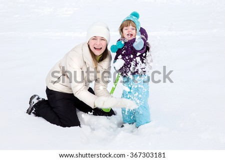 Happy laughing toddler girl wearing a white down jacket  in a beautiful snowy winter park on Christmas day. Mother and daughter enjoying beautiful winter day outdoors. baby playing with snow - stock photo