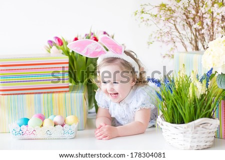 Happy laughing toddler girl with curly hair wearing a blue dress and bunny ears playing with Easter presents, eggs and colorful spring flowers, on white background
