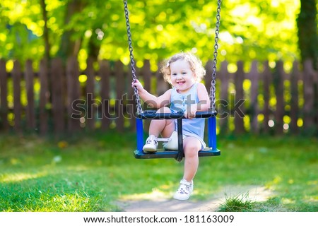 Happy laughing toddler girl with curly hair wearing a blue dress having fun on a swing enjoying a hot sunny summer day on a playground in a park - stock photo