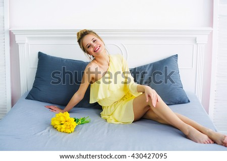 Happy laughing woman in yellow fashion dress posing with bunch of tulips on her bed - stock photo
