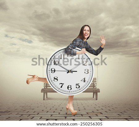 happy laughing woman with big white clock running in a park and waving hand - stock photo
