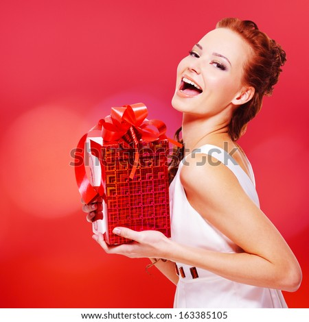 Happy laughing woman with birthday present in hands posing over red background