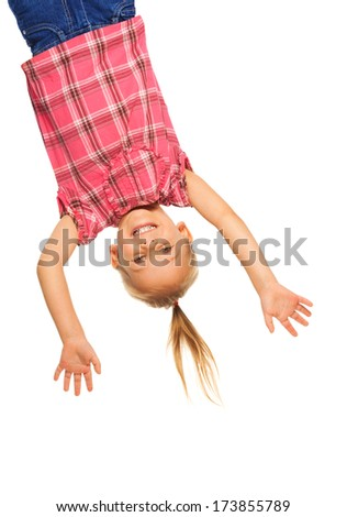 Happy laughing 4 years old girl hanging upside down isolated on white with smile on her face - stock photo