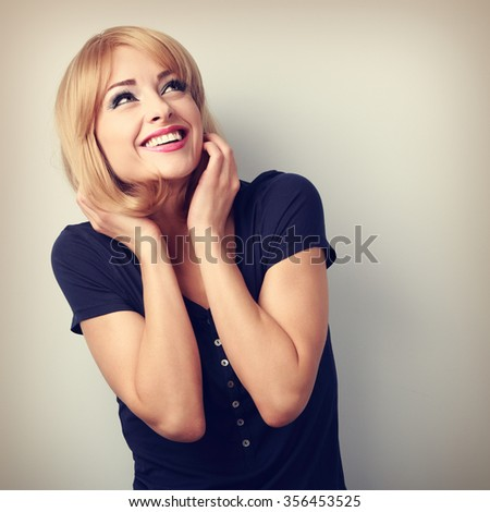 Happy laughing young woman with blond hair style looking up. Toned portrait - stock photo