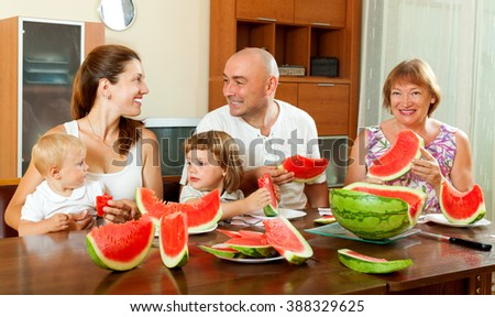 Happy laughting family having watermelon behind the table in living room