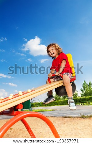 Happy lauging little three years old child sitting on the seesaw - stock photo