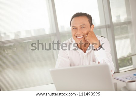 Happy leader sitting at his office and looking at camera - stock photo