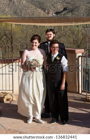 Happy lesbian couple at civil union with rabbi - stock photo