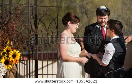 Happy lesbian couple with rabbi in civil union ceremony