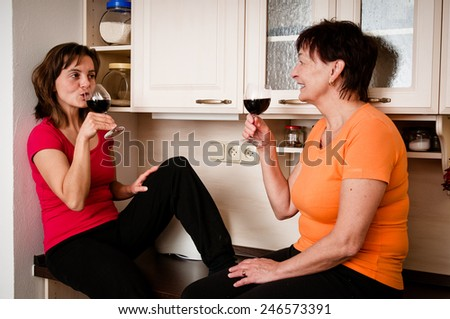 Happy life - mother and daughter drinking wine - stock photo