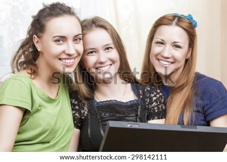 Happy Lifestyle Concept. Three Best Caucasian Girlfriends Sitting Together Embraced with Laptop. Indoors Shot. Horizontal Image Orientation - stock photo