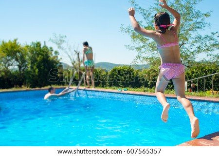 Happy little active girl jumping into stock photo edit - Swimming pool girl christmas vacation ...