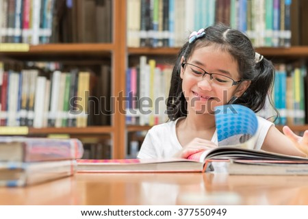 Happy little asian child girl w/ eyeglasses reading book school background: Lovely cute young student kid opening flipping book in archive resource collection room: National library lover month week - stock photo