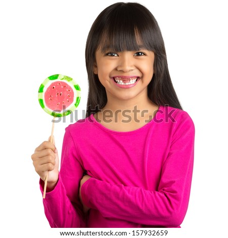 Happy little asian girl and broken teeth holding a lollipop, Isolated over white - stock photo